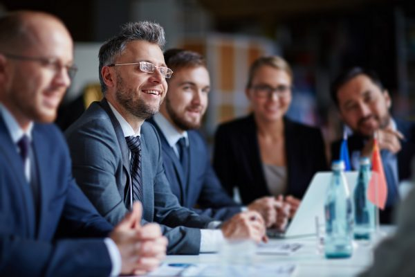 Successful businesspeople sitting at conference or seminar during lecture